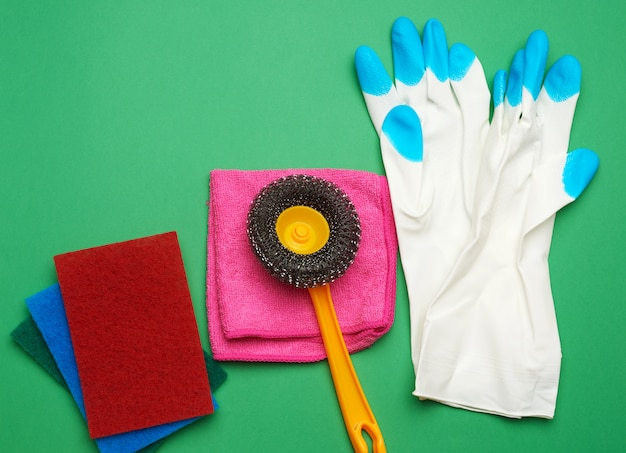 White rubber gloves for cleaning, multi-colored sponges, brushes on a green background,  flat lay