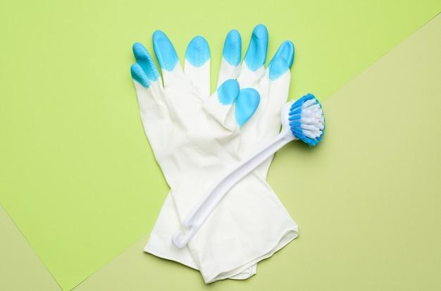 Белые резиновые перчатки для чистки, кисти на зеленом, плоской формы