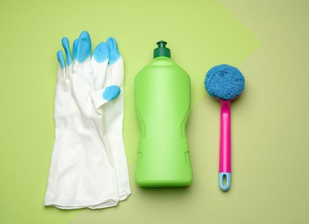 Белые резиновые перчатки для чистки, розовые щетки и чистящая жидкость в пластиковой бутылке на зеленом, вид сверху