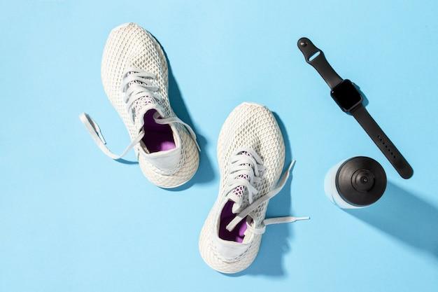 아침 해의 자연 채광 아래 파란색 배경에 흰색 운동 화, 스포츠 시계 및 물병. 조깅, 달리기, 열심히 운동의 개념입니다. 배너. 평평한, 최고 veiw