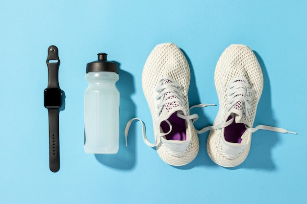白いランニングシューズ、スポーツ時計、朝の太陽の自然光の下で青い背景に水のボトル。ジョギング、ランニング、ハードトレーニングの概念。バナー。フラットレイ、トップビュー