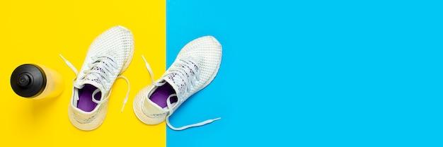 抽象的な黄色と青の表面に白いランニングシューズと水のボトル。ランニング、トレーニング、スポーツの概念。 。フラット横たわっていた、トップビュー