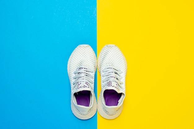 抽象的な黄色と青の表面に白いランニングシューズ。ランニング、トレーニング、スポーツの概念。 。フラット横たわっていた、トップビュー