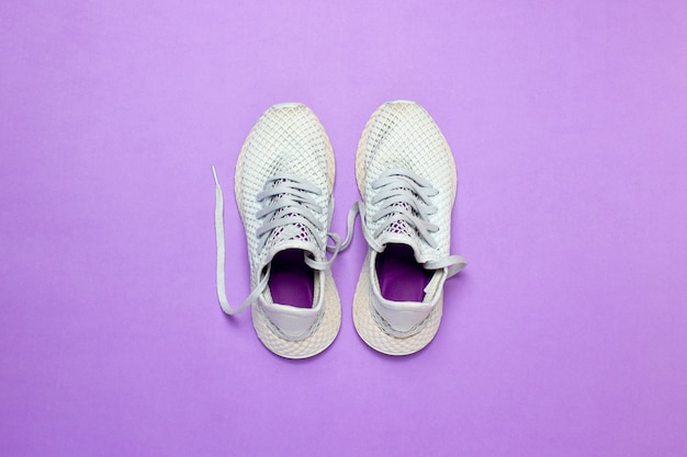 White running shoes on a purple surface. concept of running, training, sport. . flat lay, top view