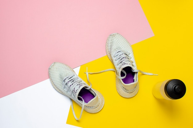 White running shoes and a water bottle on an abstract colorful surface. concept of running, training, sport. . flat lay, top view