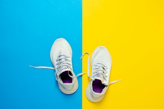White running shoes and a water bottle on an abstract yellow and blue background. concept of running, training, sport.