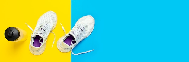 White running shoes and a water bottle on an abstract yellow and blue surface. concept of running, training, sport. . flat lay, top view