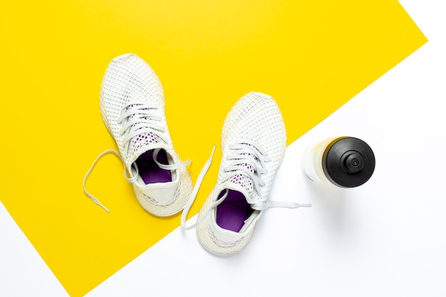 White running shoes and a water bottle on an abstract yellow-white background. concept of running, training, sport.