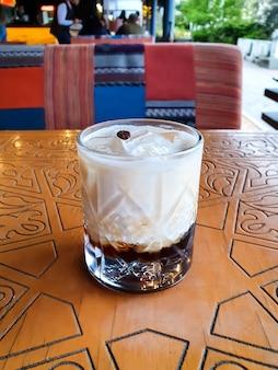 Белый русский коктейль, алкогольный коктейль, алкогольный напиток на деревянном столе в ресторане