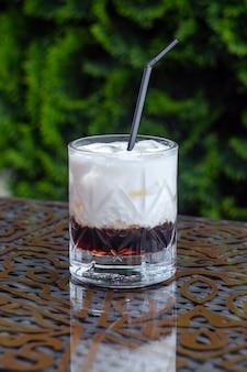 Белый русский коктейль с трубочкой, алкогольный коктейль, алкогольный напиток на столе в ресторане, коктейль с кофейным ликером и льдом в стакане, летнее кафе
