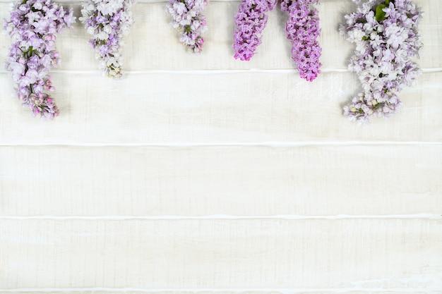 Белый деревенский деревянный фон с сиреневыми цветами и копией пространства