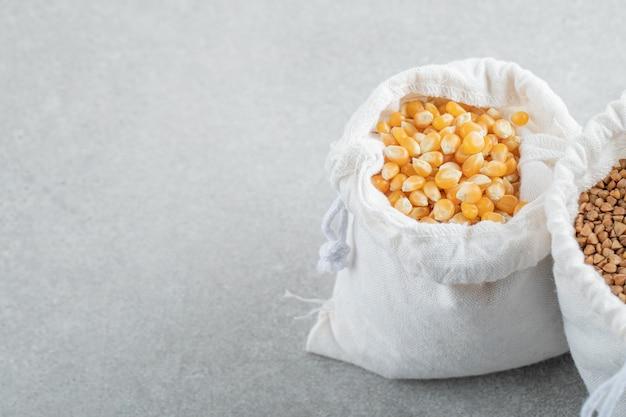 Un sacco bianco pieno di chicchi di mais e grano saraceno su uno sfondo di marmo.