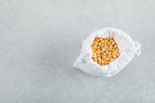 Un sacco bianco pieno di chicchi di mais su sfondo grigio.