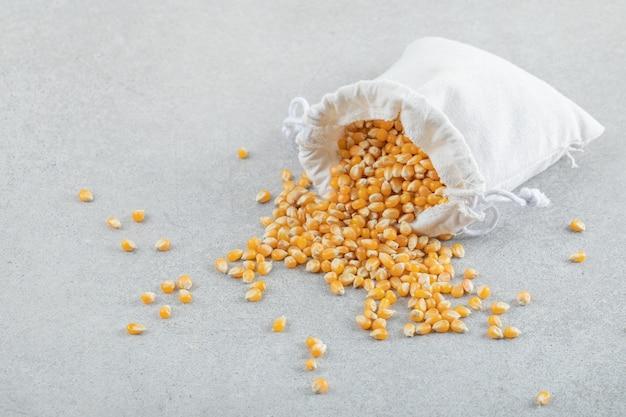 Un sacco bianco pieno di chicchi di mais su una superficie grigia.
