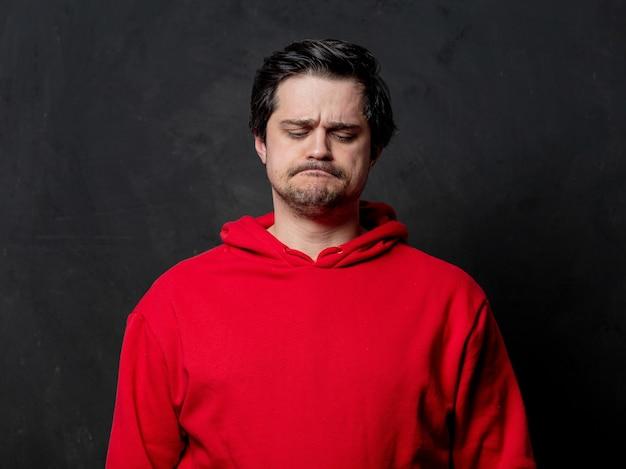 Белый грустный парень в красной толстовке на темной стене