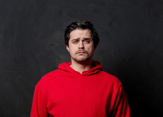 暗い壁に赤いスウェットシャツの白い悲しい男