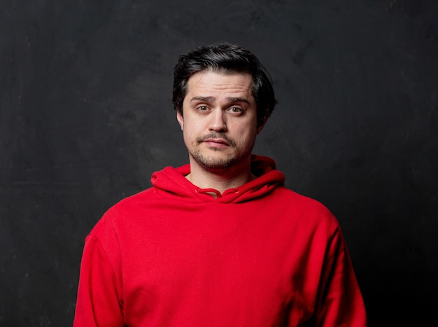 White sad guy in red sweatshirt on dark wall