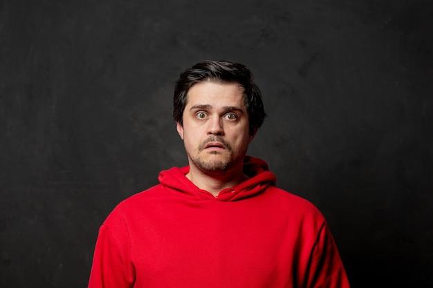 White sad guy in red sweatshirt on dark wall
