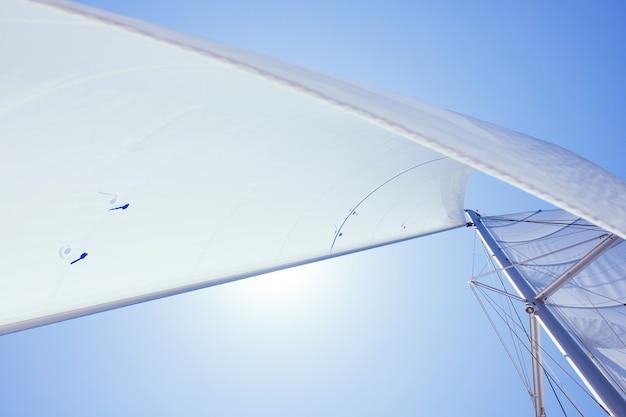 Белый парус парусной лодки против неба паруса речной парусной яхты на ветру против голубого неба