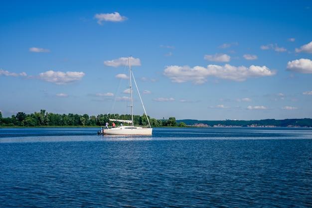 曇りの日の川の白い帆船。