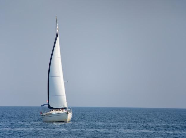 Белая парусная яхта в море. прекрасный летний морской пейзаж.