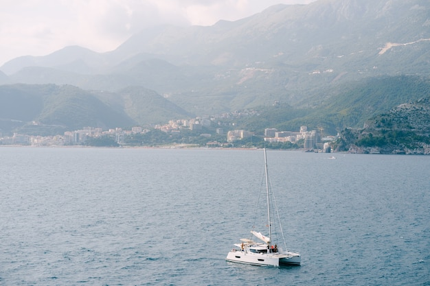 Белая парусная яхта плывет по морю против города в горах