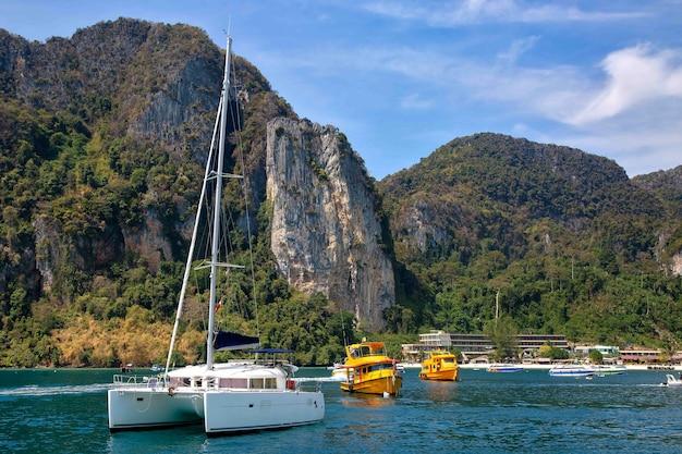 피피 섬 해안선과 여객 모터 보트의 배경에 바다에서 화이트 세일링 요트