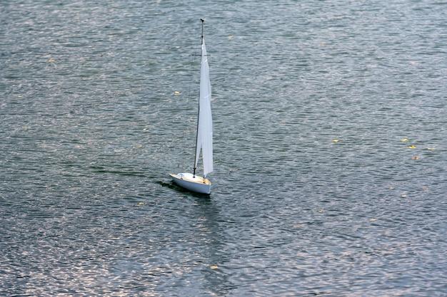 Белая модель парусной яхты, плавающие в озере.