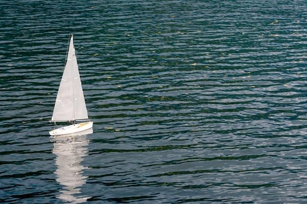 湖に浮かぶ白いセーリングヨットモデル。