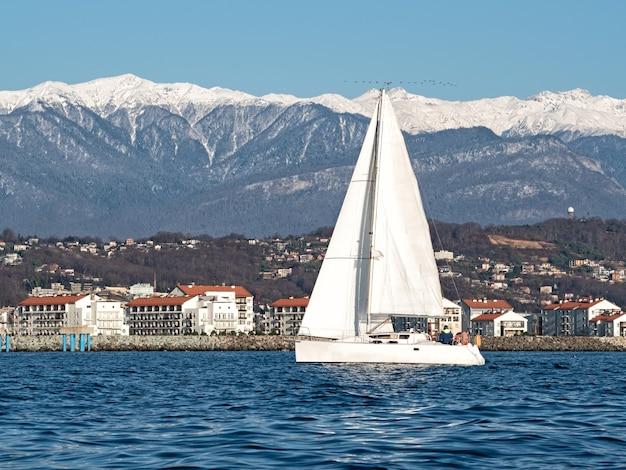 해안과 산 배경에서 바다 물에 흰색 항해 요트