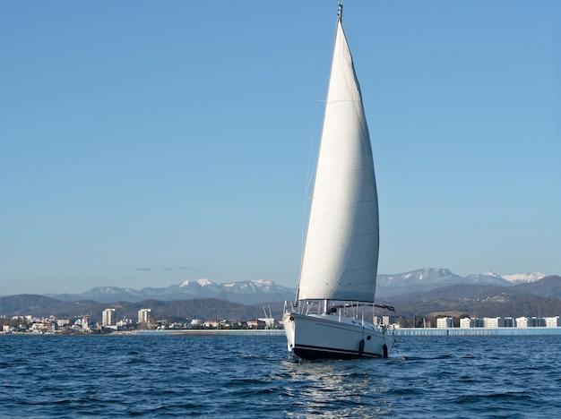 해안 배경에서 바다 물에 흰색 항해 요트