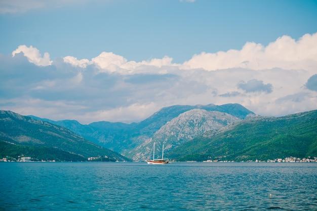 白いセーリングヨットは、明るい山々の緑の山々に対してコトル湾に沿って航行します