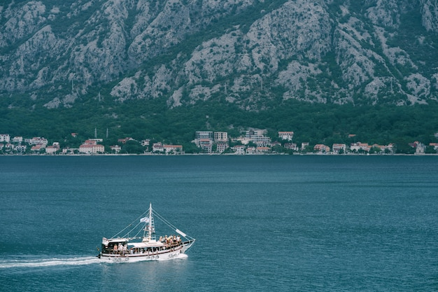 White sailing yacht with tourists on board sails along the kotor bay