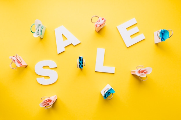 White sale alphabet surrounded with miniature shopping bags on yellow backdrop
