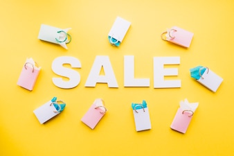 White sale text surrounded with small shopping bags on yellow background