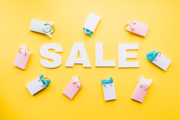 노란색 배경에 작은 쇼핑백으로 둘러싸인 흰색 판매 텍스트