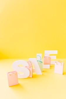 노란색 바탕에 작은 분홍색 쇼핑백과 흰색 판매 단어