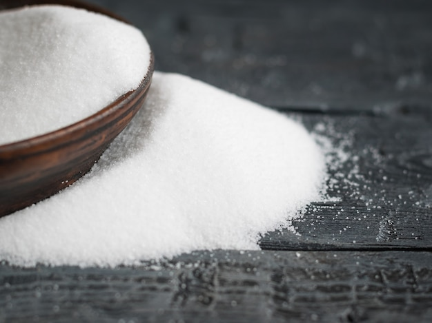 White salt, finely ground poured from a clay bowl on wooden table