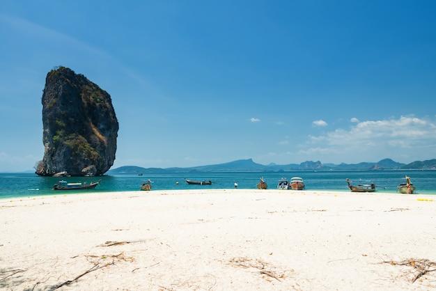 Белый песок и деревянные лодки с длинным хвостом на бирюзовом андаманском море на острове пода с голубым небом и ко пода нок, краби, таиланд. известные туристические путешествия летние каникулы на юге таиланда.