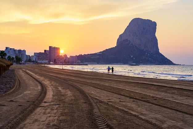 海岸沿いを歩いているカップルと日没時の白い砂浜。カルペアリカンテ。