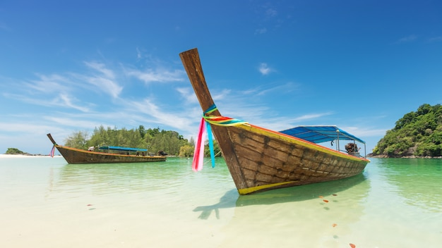 White sand beach and long tail boat at kham tok island (koh kam tok), the beautiful sea ranong province, thailand