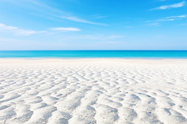 White sand curve or tropical sandy beach with blurry blue ocean and blue sky background