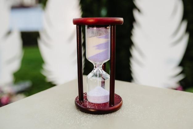 Песочные часы из белого песка из коричневого дерева на столе