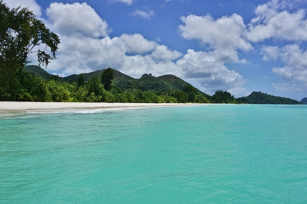 White sandy beach withturquoise water and blue sky with clouds, indian ocean, praslin island, seychelles, africa