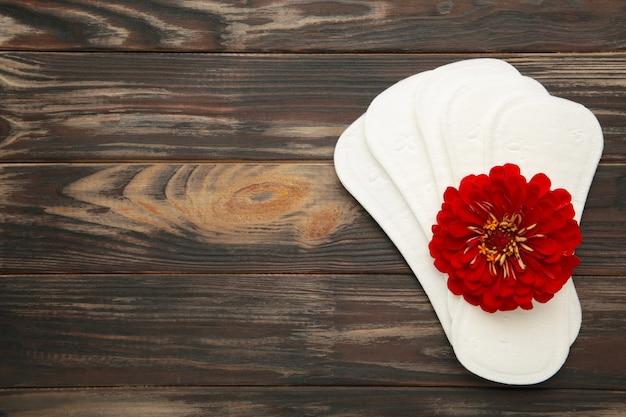 Белая прокладка, гигиеническая защита на коричневом фоне. гинекологический менструальный цикл. цветок розы лежит на менструальных подушечках. первая менструация. вертикальное фото