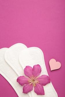 Белая прокладка, гигиеническая защита на фиолетовом фоне. гинекологический менструальный цикл. цветок розы лежит на менструальных подушечках. первая менструация. вертикальное фото