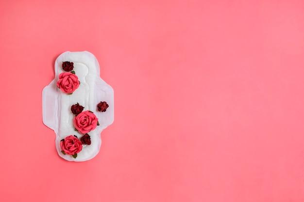 それ、女性の健康や体の肯定的な概念に赤とピンクの花を持つ白い生理用ナプキン。