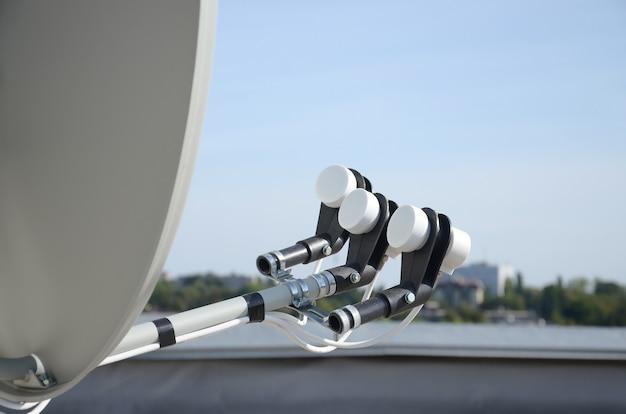 주거용 건물 옥상 콘크리트 벽에 3 개의 변환기가 장착 된 흰색 위성 접시. 위성 텔레비전 광고