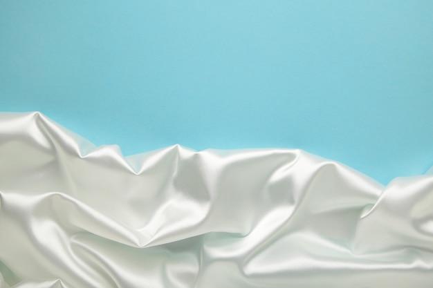 Белая атласная ткань на синем фоне