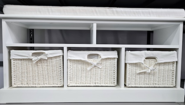 В магазине продается белая мебель в скандинавском стиле с плетеными ящиками и пуфом.